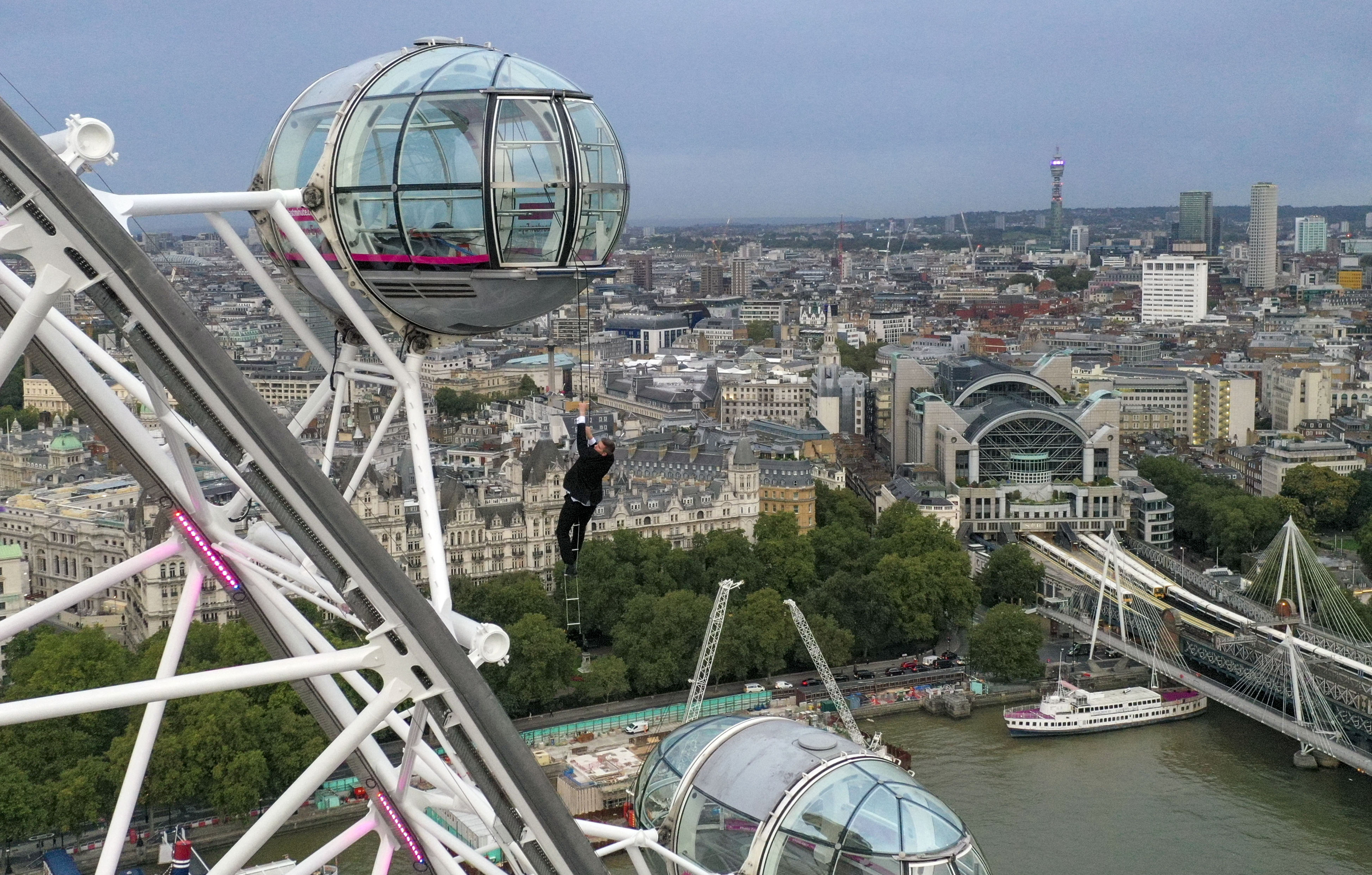 <p>A man dressed as Britain's most famous secret service agent, James Bond, is silhouetted against the London skyline as he climbs the outside of a pod on the lastminute.com London Eye, the landmark tourist attraction in central London, ahead of the world premiere of No Time To Die, the latest instalment in the Bond franchise. Picture date: Tuesday September 28, 2021.</p>
