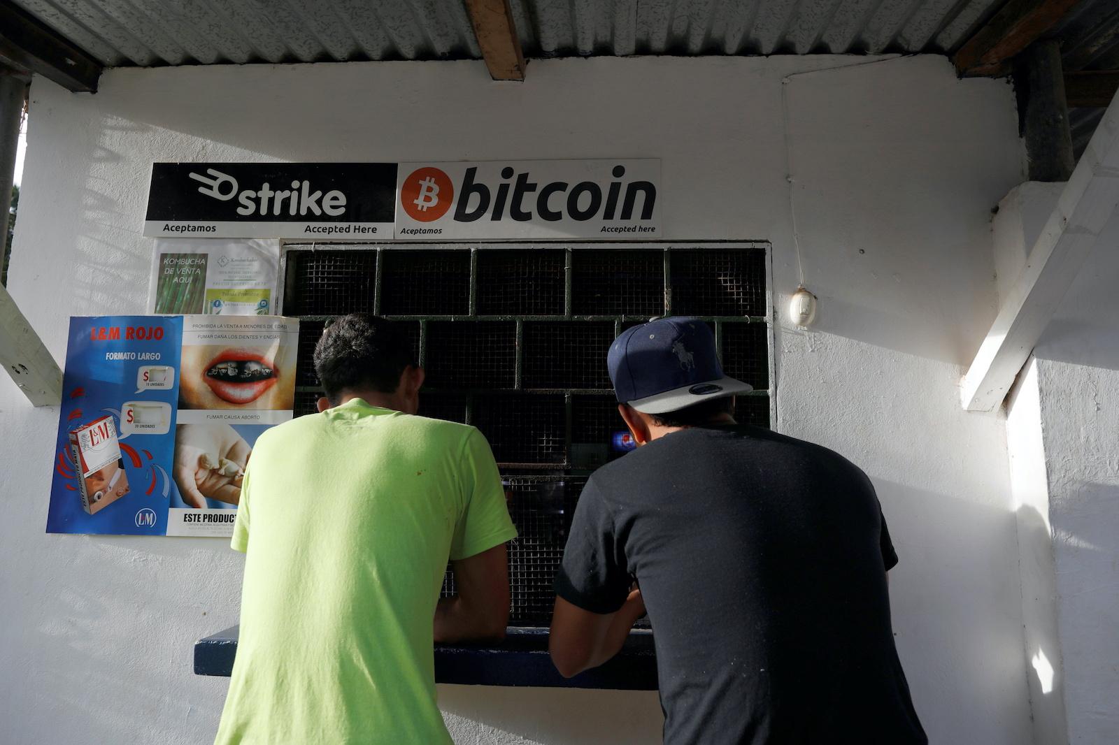 Men buy snacks at a store where bitcoins are accepted at El Zonte Beach in Chiltiupan, El Salvador June 16, 2021. REUTERS/Jose Cabezas - RC2Z1O9MEUEP