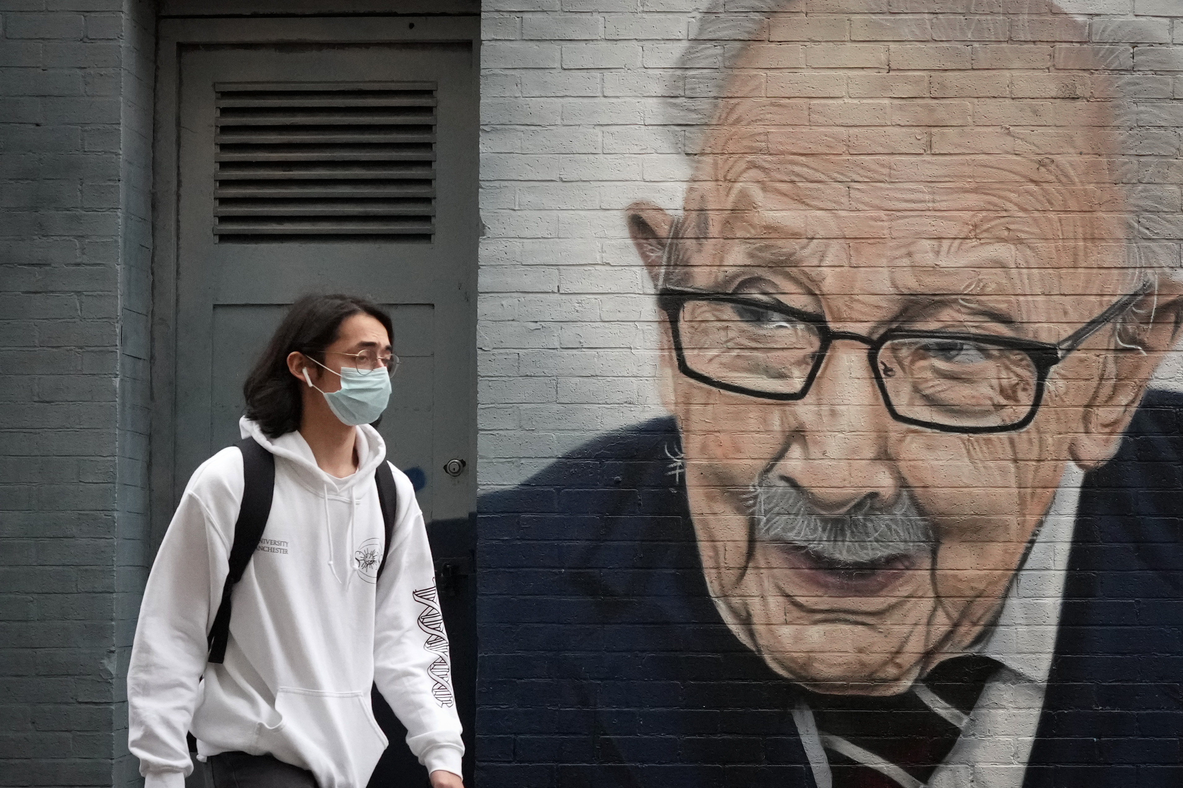 <p>MANCHESTER, ENGLAND - SEPTEMBER 13: A member of the public wears a pandemic face mask as he walks past a mural of Captain Tom Moore, ahead of the prime minister announcing the government's Covid-19 winter strategy on September 13, 2021 in Manchester, England. Tomorrow, British Prime Minister Boris Johnson will set out his plan to manage Covid-19 through the winter, including what actions would need to be taken if the NHS hospital system were at risk of being overwhelmed. (Photo by Christopher Furlong/Getty Images)</p>