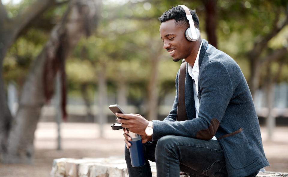 一位年輕商人在城市中使用智能手機和耳機的照片