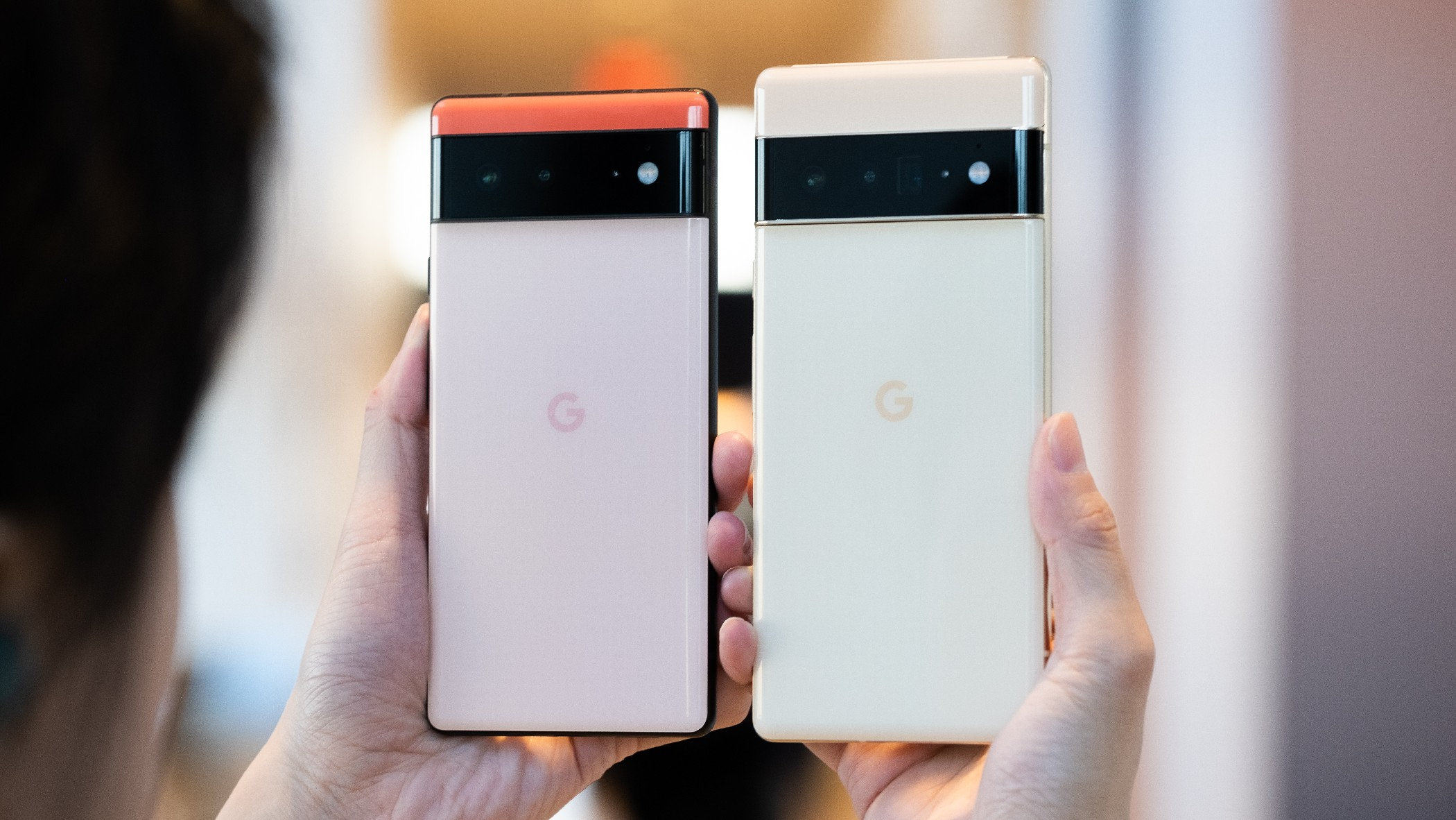 The Google Pixel 6 and 6 Pro held up in mid-air with their camera bars facing out.