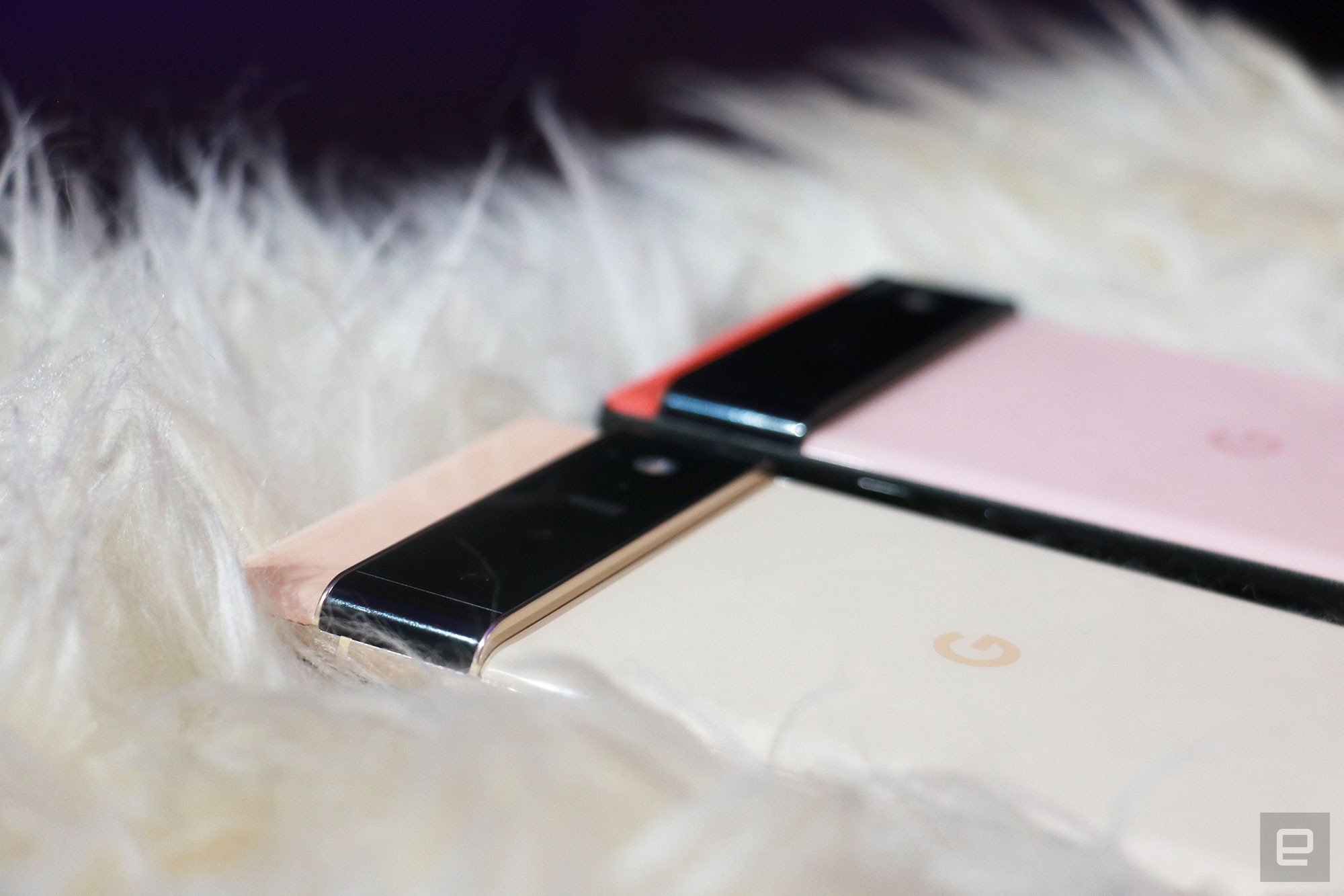Close ups of the Pixel 6 and Pixel 6 Pro camera bumps as the phones are laid out on a furry surface.