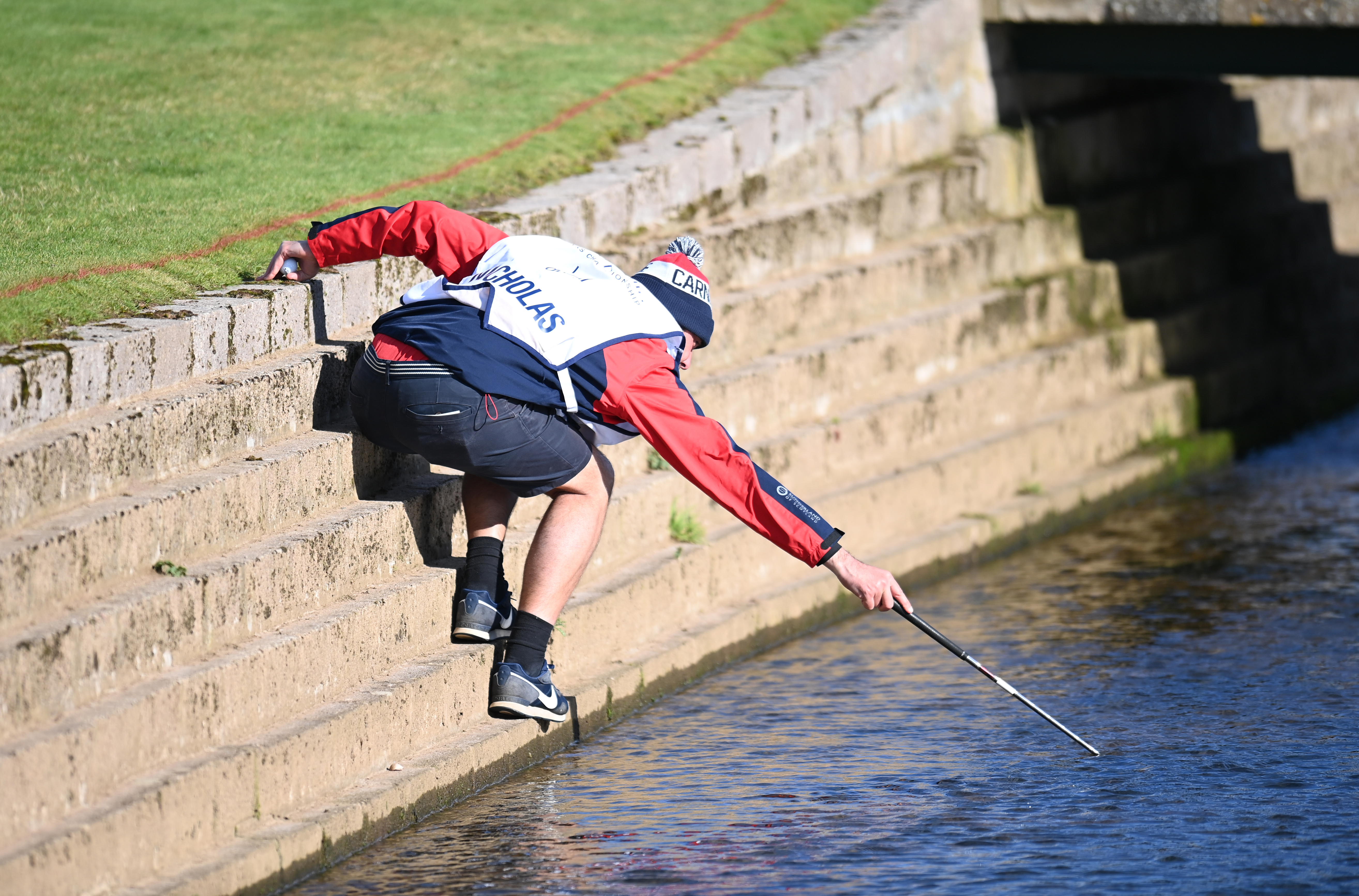 <p>A caddie retrieves a ball from the water during day two of the Alfred Dunhill Links Championship at Carnoustie. Picture date: Friday October 1, 2021.</p>