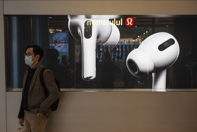 HONG KONG, CHINA - 2020/02/19: A man stands in front of American multinational technology company Apple store displaying the Airpods Pro banner at its entrance in Hong Kong. (Photo by Budrul Chukrut/SOPA Images/LightRocket via Getty Images)