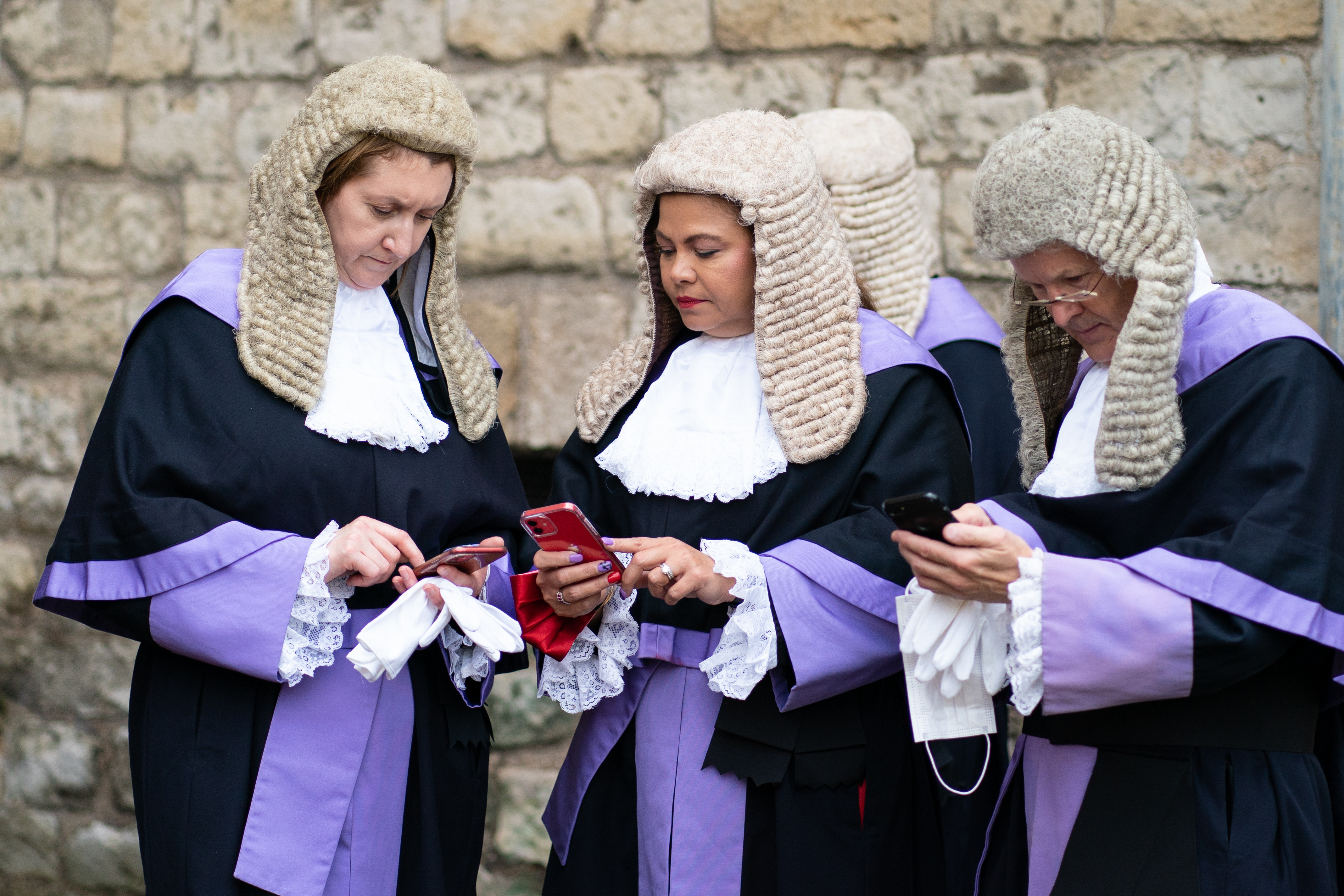 <p>Judges use their phones as they wait outside the west door of Westminster Abbey, London, ahead of the annual Judges Service, which marks the start of the new legal year. Picture date: Friday October 1, 2021.</p>