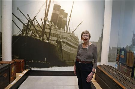 """U.S. author Fuentes from Sarasota, Florida, poses next to a photo of the Belgenland while visiting the """"Millions of People, One Dream"""" exhibition at the Red Star Line Museum in Antwerp"""