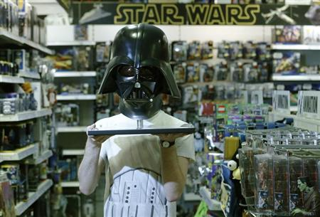 Employee Simon Domoney poses with a scale replica of Star Wars character Darth Vader's helmet at the Forbidden Planet memorabilia and comic store in London May 11, 2013. REUTERS/Luke MacGregor/Files
