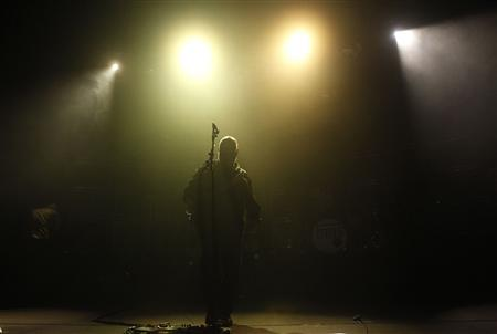 Black Francis of the American band the Pixies stands under stage lights during a performance at Lisbon Coliseum