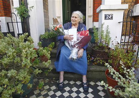 File photograph shows British novelist Lessing sitting on the doorstep of her house in London