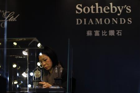 A member of staff checks a display prior to the exhibition sale of Sotheby's Diamonds during Sotheby's Beijing Art Week in Beijing