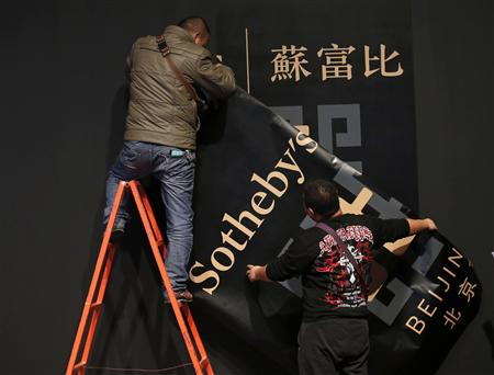 Workers install Sotheby's large banner on a wall during Sotheby's Beijing Art Week in Beijing