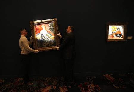 Staff hang 'La Parisienne De Montmartre' by Kees Van Dongwen at the exhibition sale of 'Modern Masters' during Sotheby's Beijing Art Week