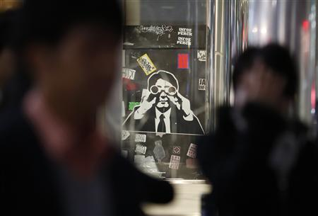 People walk past a sticker art made by an artist known as 281 Antinuke, designed in the likeness of Japan's Prime Minister Abe, along a street in Tokyo