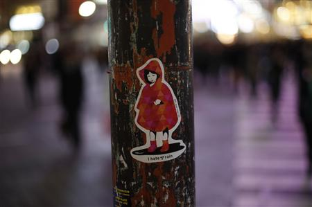 Sticker art made by an artist known as 281 Antinuke is seen on a traffic light on a street in Tokyo