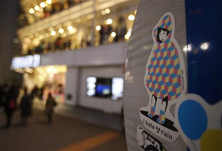 Sticker art made by an artist known as 281 Antinuke, is seen on the back of a traffic signboard on a street in Tokyo