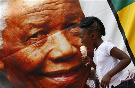 A girl eats an incecream while passing by a giant portrait of Nelson Mandela outside of his house on Vilakazi Street in Soweto