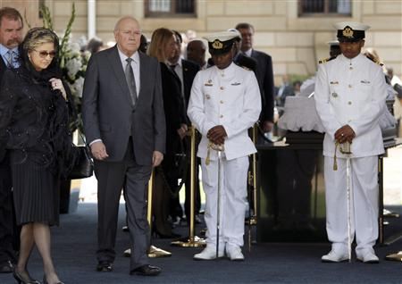 Former South African president de Klerk, who shared 1993 Nobel Peace Prize with former South African President Nelson Mandela, walks with his wife Elita, after paying their respects at Mandela's coffin in Pretoria