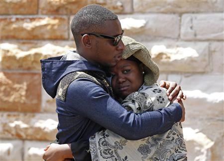 Man and woman comfort each other after paying their respects at coffin of former South African President Nelson Mandela as Mandela lies in state in Pretoria