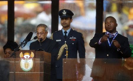 India's President Mukherjee speaks at the podium as a sign language interpreter punches air beside him during a memorial service for late South African President Nelson Mandela in Johannesburg