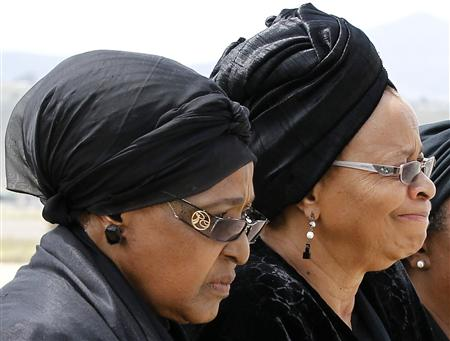Winnie walks with Graca as Mandela's flag-draped coffin arrives at the Mthatha airport