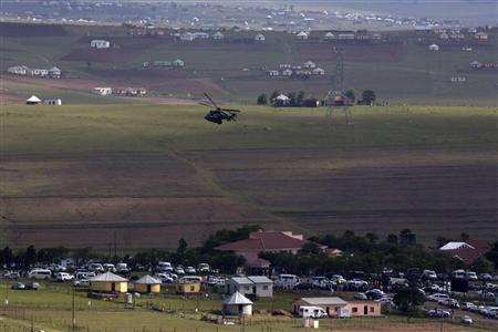 A military helicopter patrols the area as the hearse carrying the coffin of former South African President Nelson Mandela is escorted by a funeral procession after entering his home in Qunu