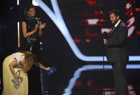 Sandler accepts the award for favorite comedic movie actor as presenter Barrymore bows at the 2014 People's Choice Awards in Los Angeles