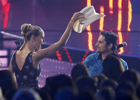 "Model Klum tries to replace singer Paisley's hat as he performs ""The Mona Lisa"" at the 2014 People's Choice Awards in Los Angeles"