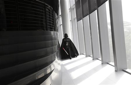 "An entertainer dressed as Darth Vader from ""Star Wars"" walks down the corridor to pose for the media during the opening of Lucasfilm's new animation production facility, the Sandcrawler, in Singapore"