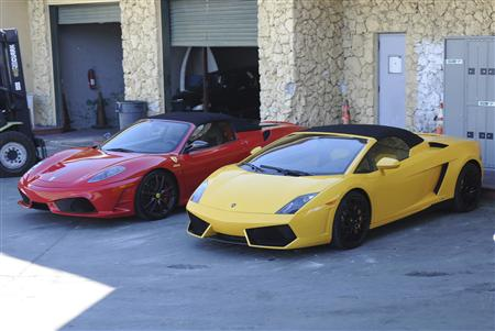 Two sports cars sit in a police impound lot in Miami Beach