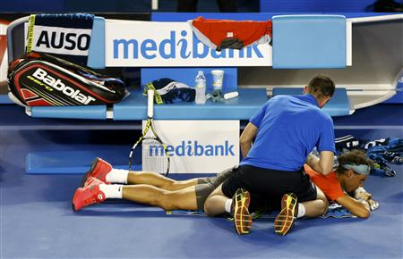 Rafael Nadal of Spain receives treatment during his men's singles final match against Stanislas Wawrinka of Switzerland at the Australian Open 2014 tennis tournament in Melbourne