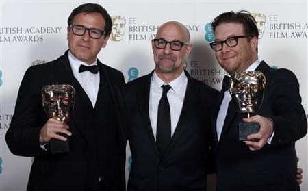 "Singer and Russell celebrate with Tucci after winning the Original Screenplay category for ""American Hustle"" at the BAFTA awards ceremony in London"