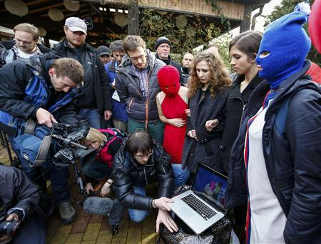Russian punk band Pussy Riot members Maria Alyokhina and Nadezhda Tolokonnikova along with masked members show a video to journalists on a laptop computer during the 2014 Sochi Winter Olympics, in Adler