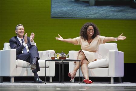 Howard Schultz, CEO of Starbucks, applauds on stage next to surprise guest Oprah Winfrey during the company's annual shareholders meeting in Seattle