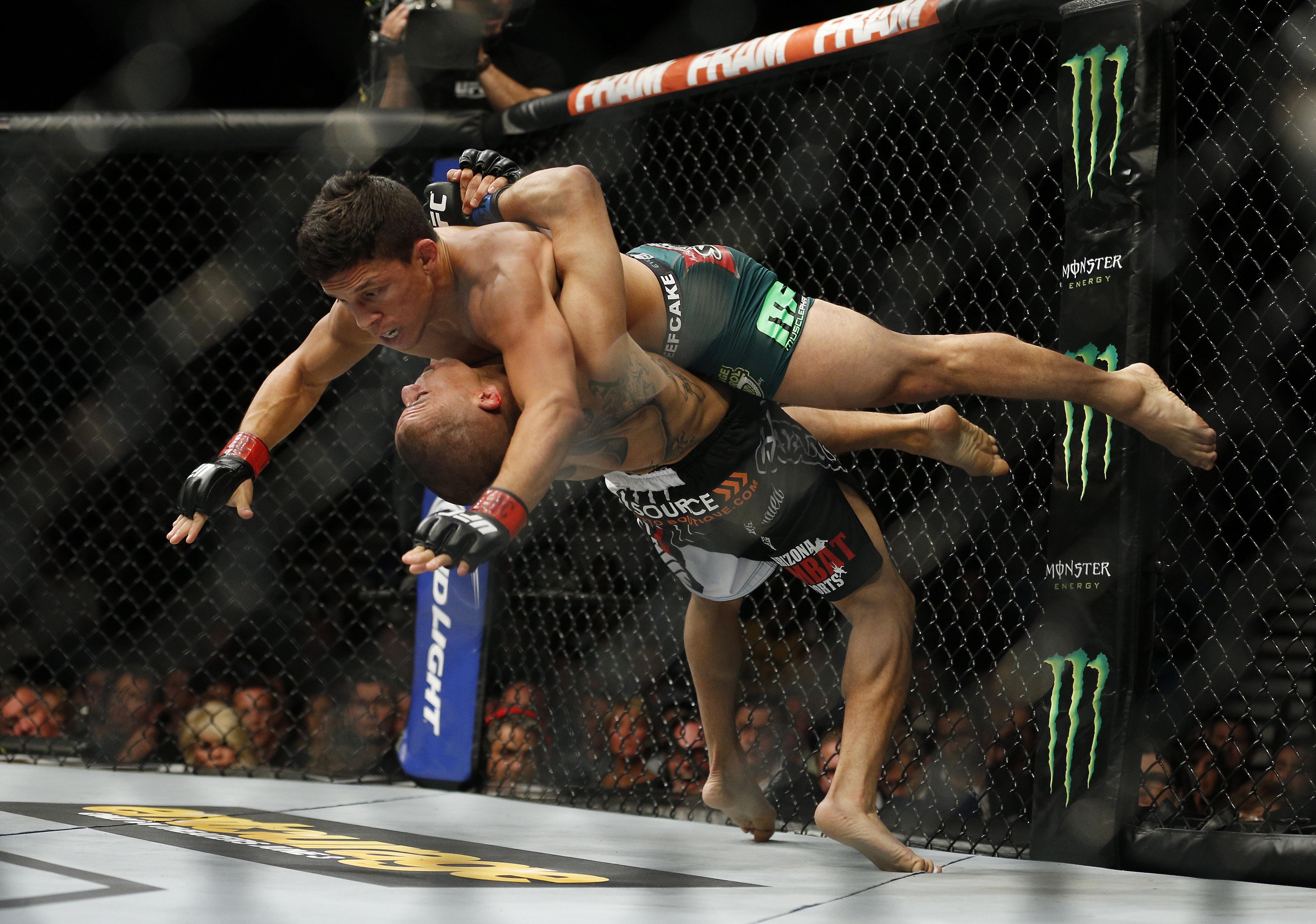 John Moraga, bottom, takes down Joseph Benavidez during their flyweight fight. (AP)