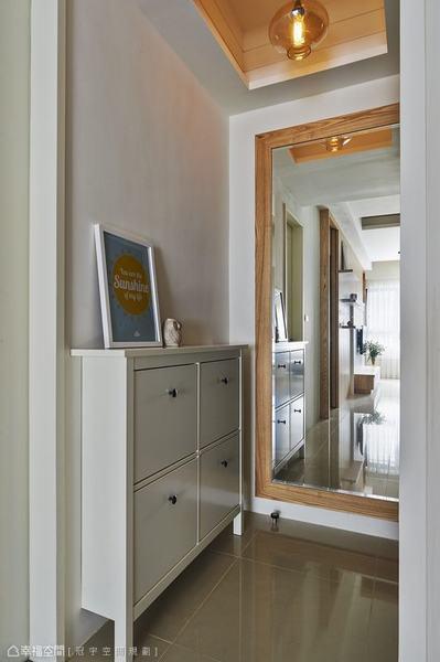 木質框定的大片穿衣鏡面於玄關處有效延續採光,預告空間的材質表現,同時藏起電箱的位置。