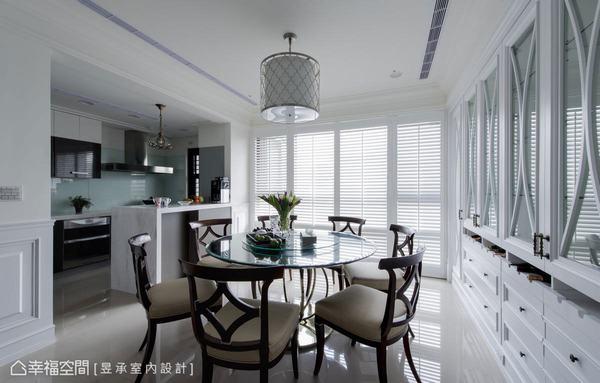 餐廚空間則呈開放式規劃,以大片白色木百葉引納光線,烘托出美式家具、燈飾與古典餐具櫃的細膩質感,詮釋美式居家的典雅風格。