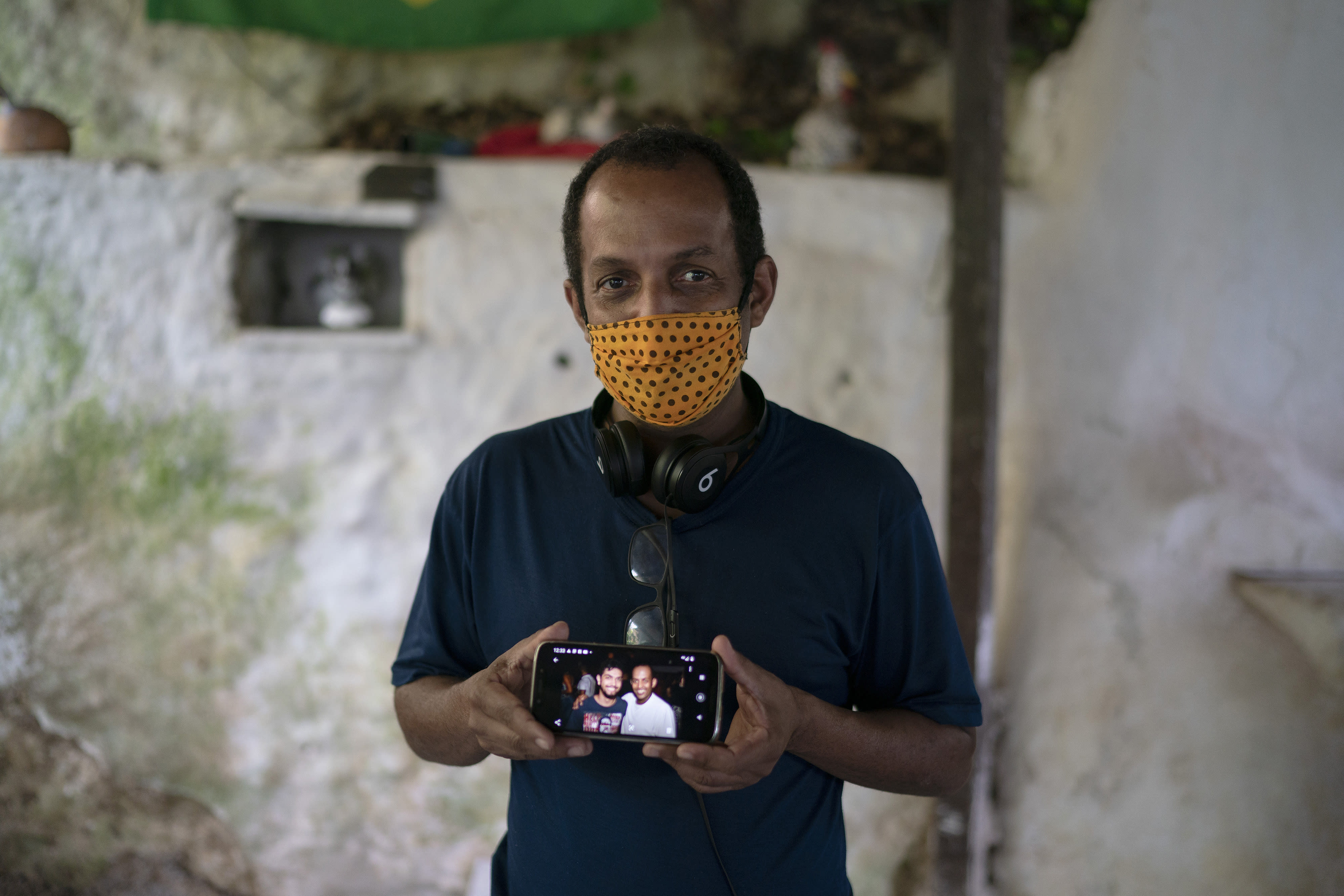 Marcio Antonio do Nascimento shows a photo of himself with his 25-year-old son Hugo do Nascimento who died from the new coronavirus, in Rio de Janeiro, Brazil, Saturday, Aug. 1, 2020. Brazil was leaping toward a grim milestone, 100,000 deaths from COVID-19, on Saturday, Aug. 8, and five months after the first reported case, the country had not shown signs of crushing the disease. (AP Photo/Leo Correa)