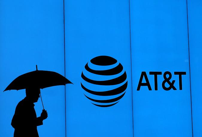 DALLAS, TEXAS - MARCH 13:  A man walks with an umbrella outside of AT&T corporate headquarters on March 13, 2020 in Dallas, Texas.  AT&T is allowing employees to work remotely from home if they have the ability to do so, as a safety measure due to COVID-19. (Photo by Ronald Martinez/Getty Images)