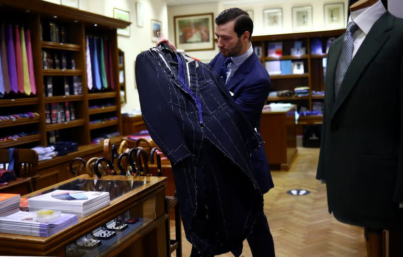 Head Shirt Cutter Tom Bradbury holds a bespoke tailcoat in the Dege & Skinner tailors on Savile Row, amid the coronavirus disease (COVID-19) outbreak, in London