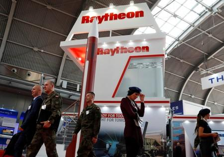 People pass the U.S. defense company Raytheon stand at an international military fair in Kielce