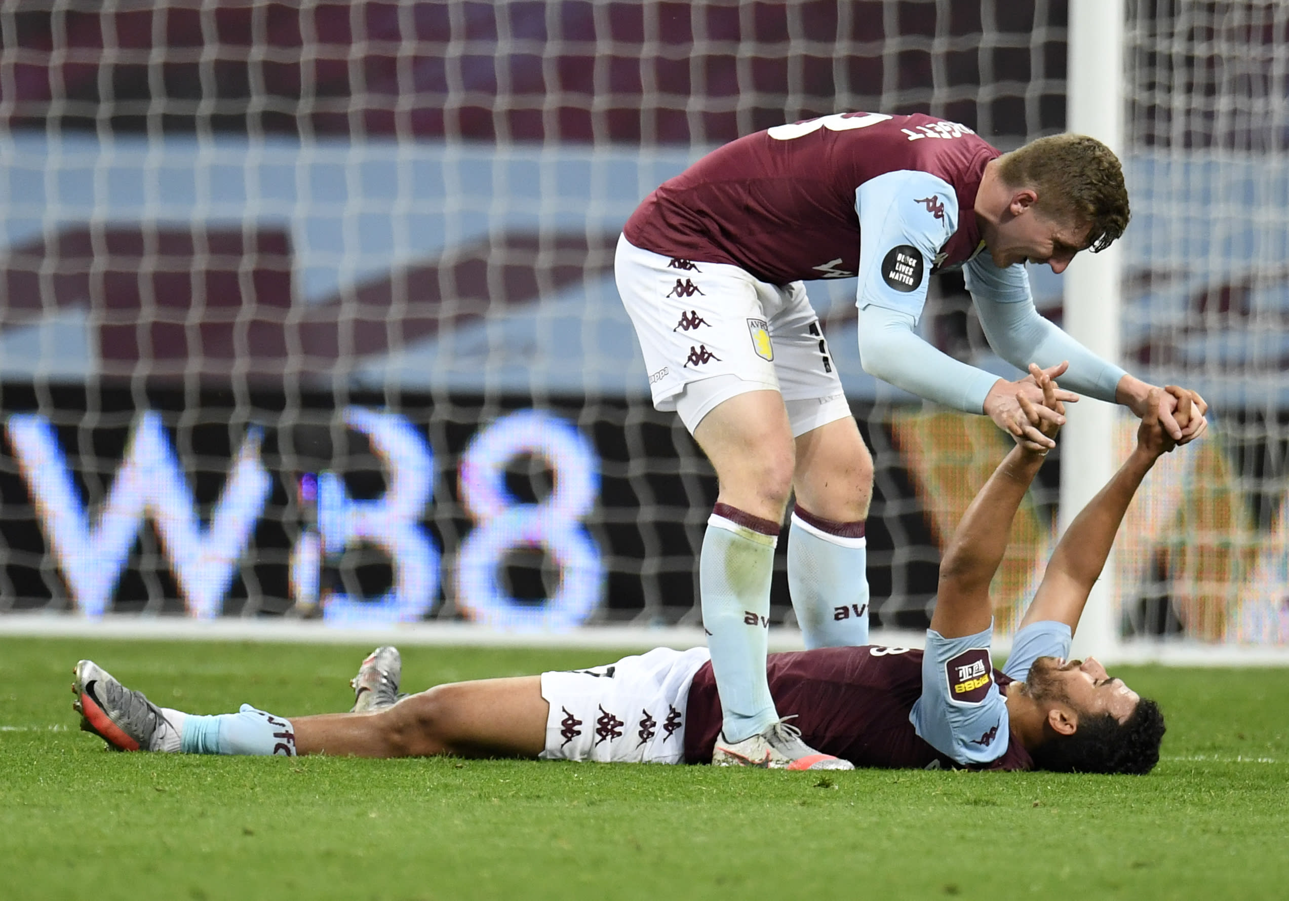 Aston Villa's Matt Targett, top, celebrates with teammate Trezeguet after the English Premier League soccer match between Aston Villa and Arsenal at Villa Park in Birmingham, England, Tuesday, July 21, 2020. (AP Photo/Peter Powell,Pool)