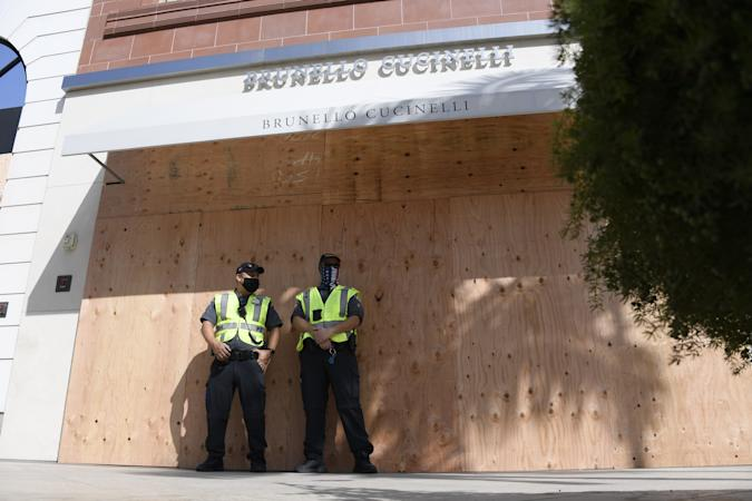 BEVERLY HILLS, CA - NOVEMBER 03: Beverly Hills police traffic officers stand guard in front of boarded up designer stores on Rodeo Drive in preparation for possible unrest on the night of U.S. presidential election on November 3, 2020 in Beverly Hills, California. Businesses in cities across the country are preparing for possible unrest as election results come in. (Photo by Kevork Djansezian/Getty Images)