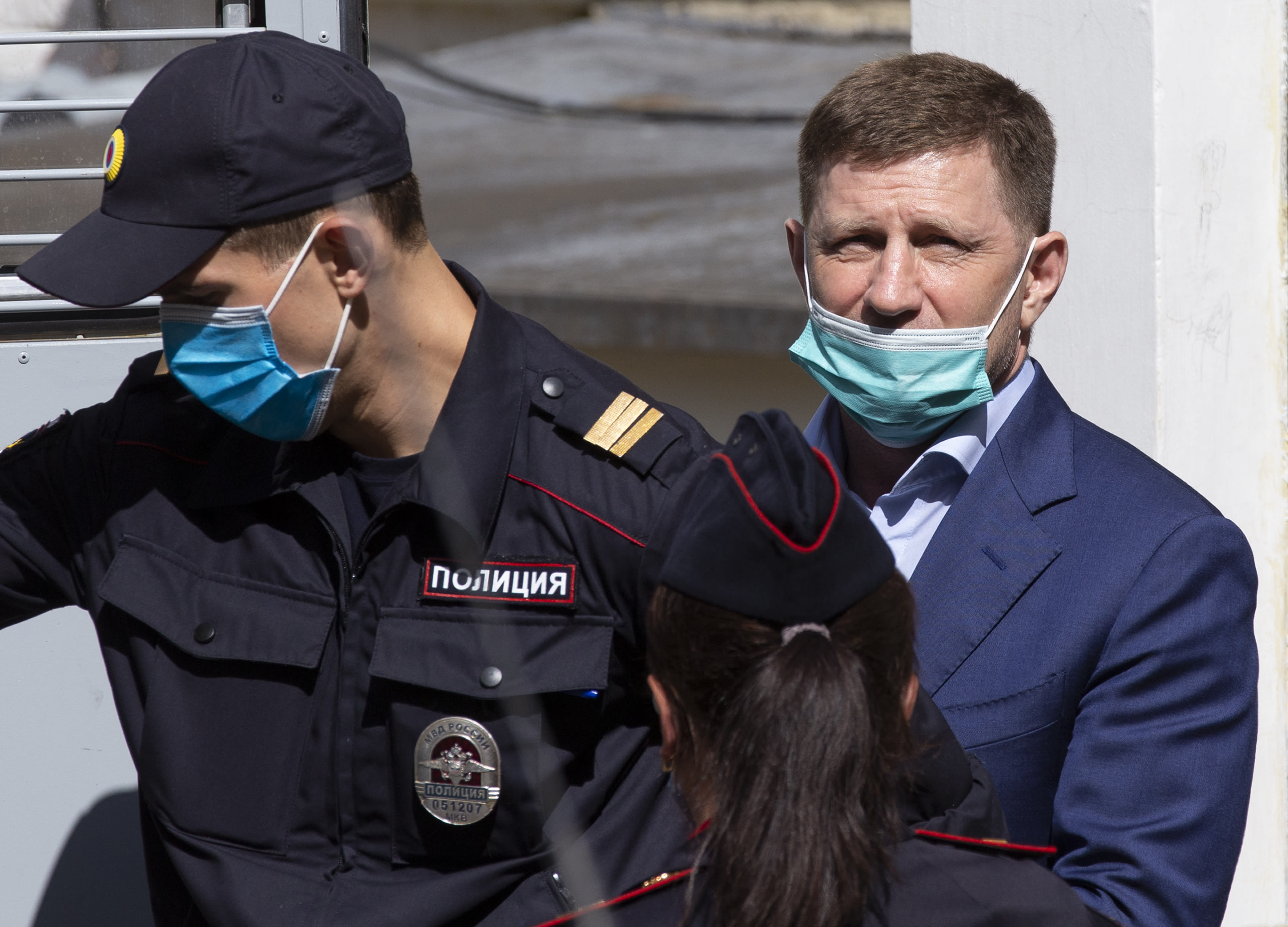A governor of the Khabarovsk region along the border with China, Sergei Furgal, right, is escorted from a court room in Moscow, Russia, Friday, July 10, 2020. A provincial governor in Russia's far east has been arrested on charges of involvement in multiple murders and was flown to Moscow. The court ordered Frugal to be jailed for two months as the investigation continues. (AP Photo/Alexander Zemlianichenko)