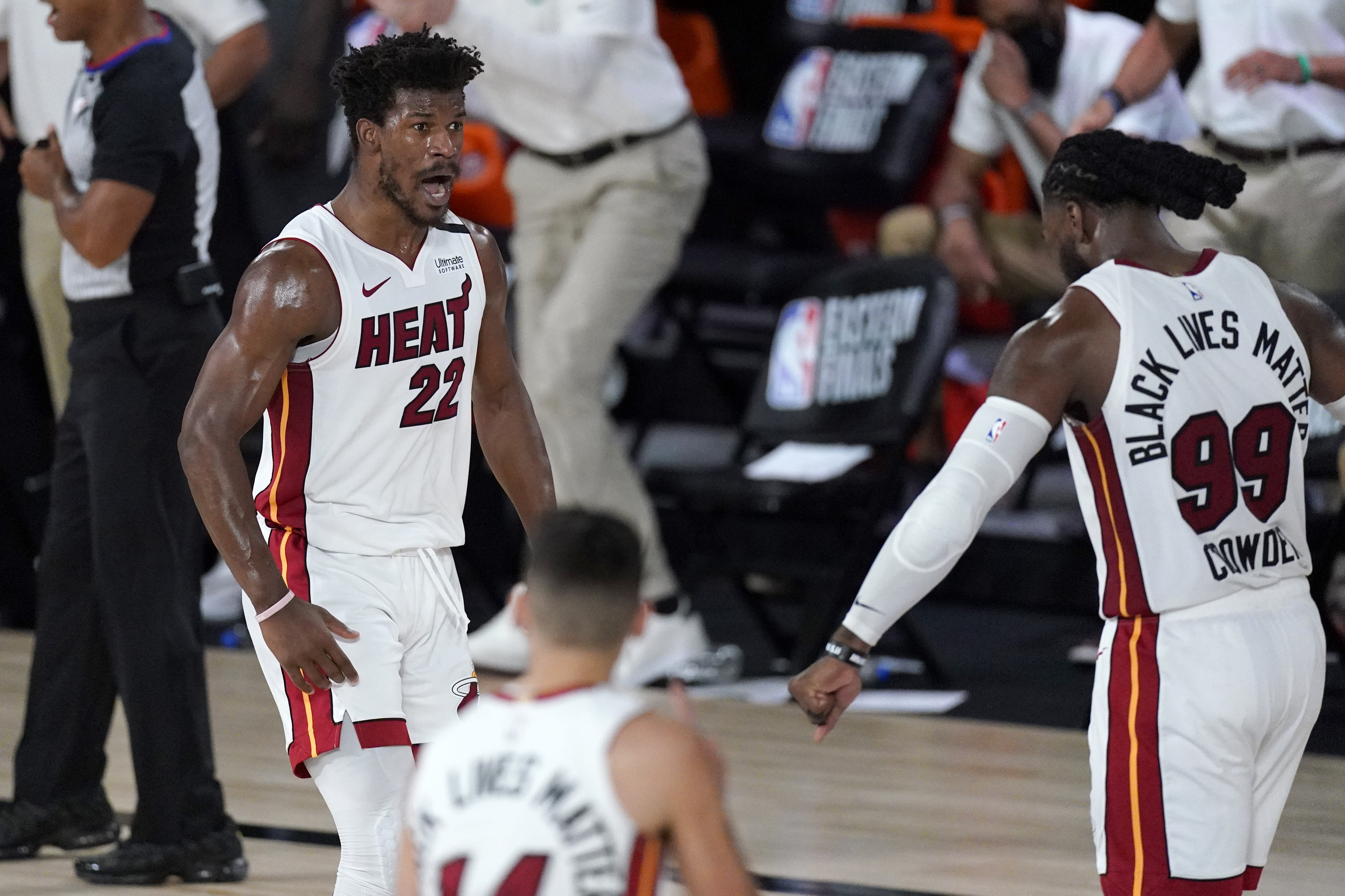 Miami Heat's Jimmy Butler (22), Tyler Herro, bottom center, and Jae Crowder (99) celebrate a game tying basket by Butler late in the second half of an NBA conference final playoff basketball game against the Boston Celtics on Tuesday, Sept. 15, 2020, in Lake Buena Vista, Fla. (AP Photo/Mark J. Terrill)