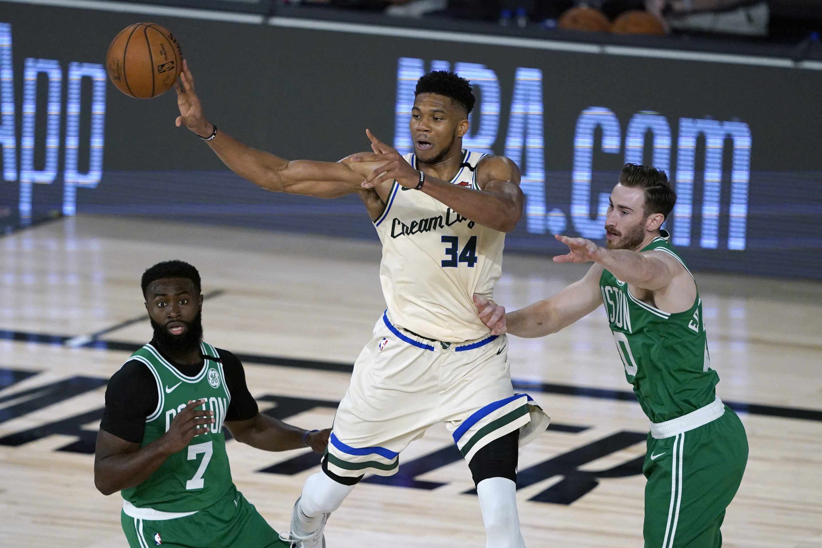 Milwaukee Bucks' Giannis Antetokounmpo (34) passes around Boston Celtics' Jaylen Brown (7) and Gordon Hayward during the first half of an NBA basketball game Friday, July 31, 2020, in Lake Buena Vista, Fla. (AP Photo/Ashley Landis, Pool)