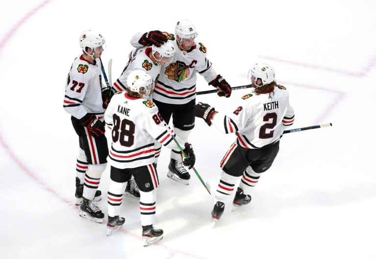 Chicago's Dominik Kubalik, center with glove on his helmet, is congratulated by Blackhawks teammates after a second-period goal in the team's NHL playoff victory over Edmonton on Saturday