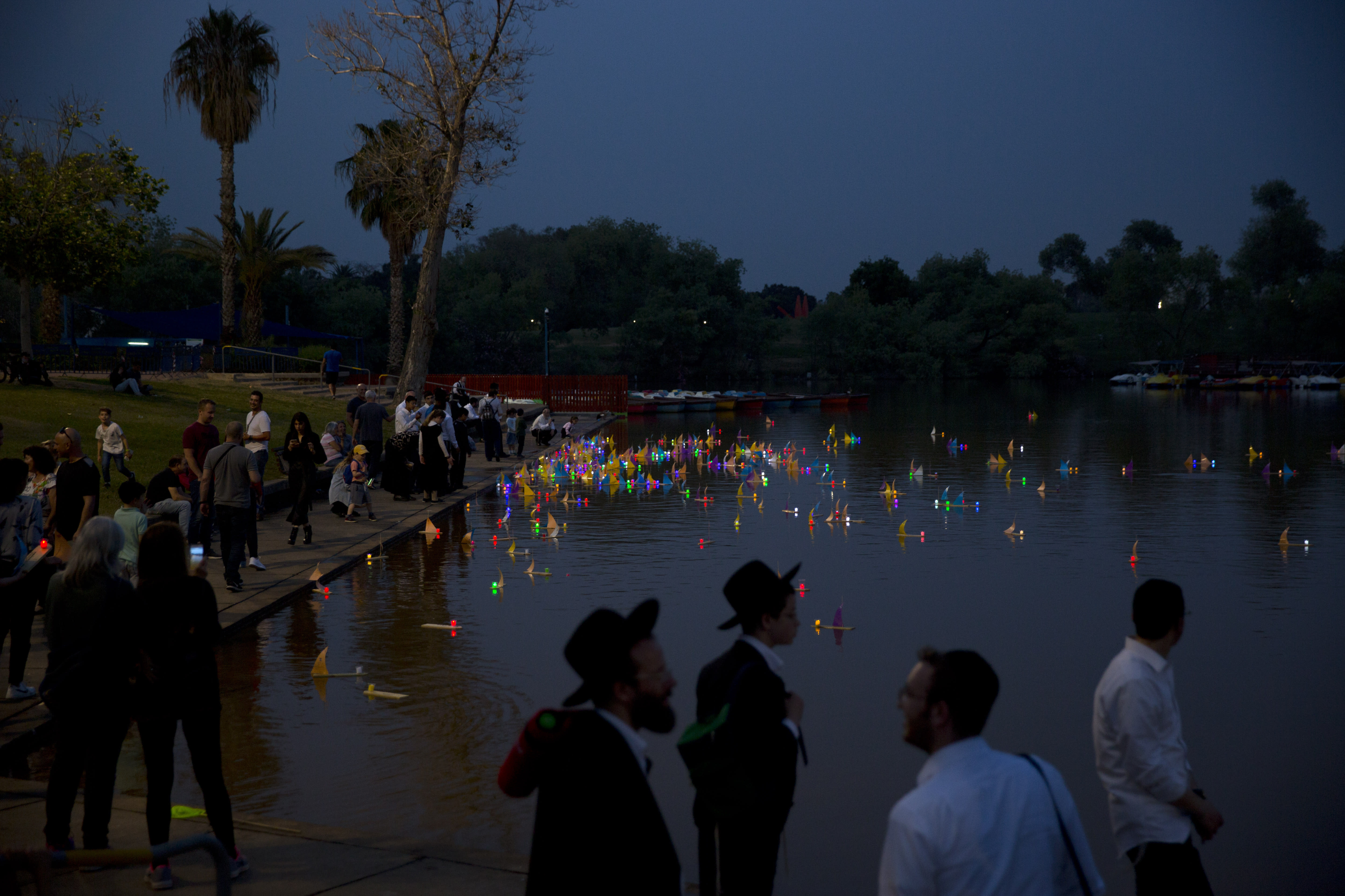 """People look on floating handmade boats with the names of Nazi concentration camps, during a ceremony marking the annual Holocaust Remembrance Day in Hayarkon park in Tel Aviv, Israel, Wednesday, May 1, 2019. Israel marking the annual Day of Remembrance for the six million Jewish victims of the Nazi genocide who perished during World War II. Hebrew reads """"to remember"""". (AP Photo/Oded Balilty)"""