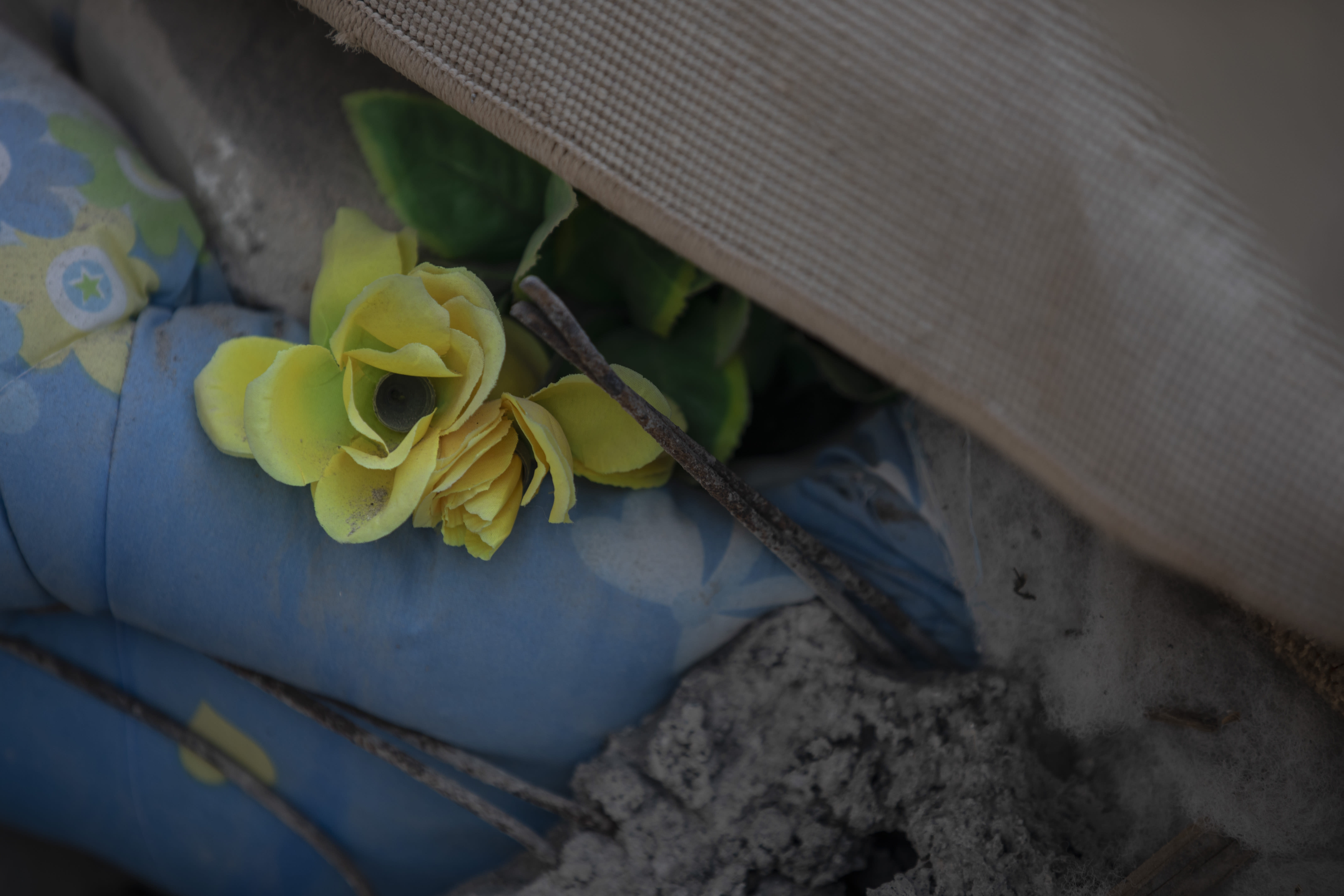 In this Wednesday, Nov. 27, 2019 photo, a plastic flower among rubbles of a collapsed building damage building in Thumane, western Albania following a deadly earthquake.(AP Photo/Petros Giannakouris)