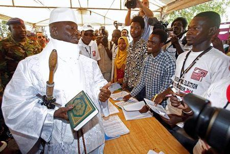 Gambian President Jammeh holds a copy of the Quran while speaking to a poll worker at a polling station during the presidential election in Banjul
