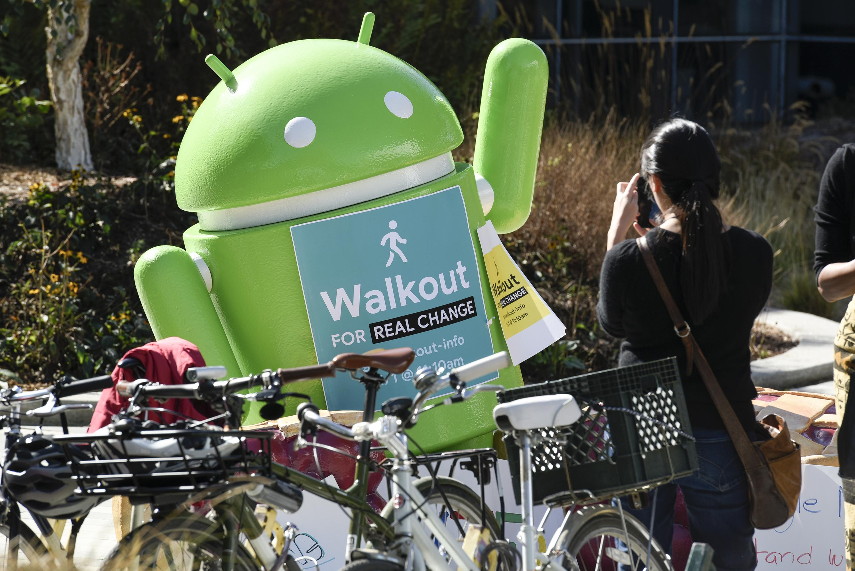 """<p>A person takes a photograph of an Android statue displaying a sign that reads """"Walkout For Real Change"""" during a protest outside Google headquarters in Mountain View, Calif., on Thursday, Nov. 1, 2018. (Photo: Michael Short/Bloomberg via Getty Images </p>"""